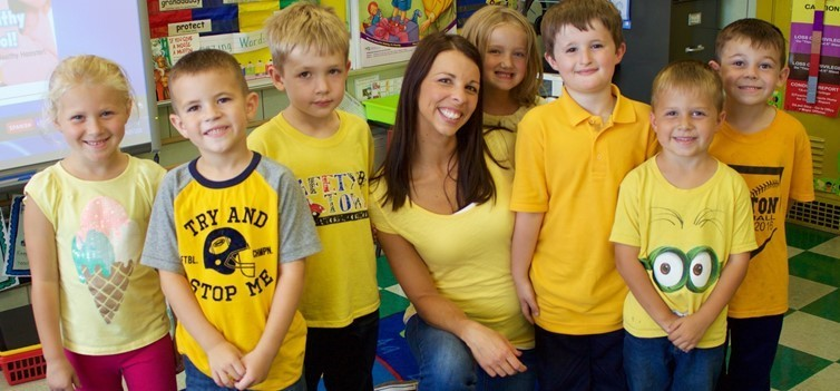 elementary kids with student all wearing yellow in classroom