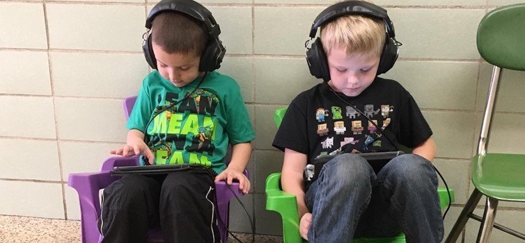 two young kids wearing headphones sitting in chairs