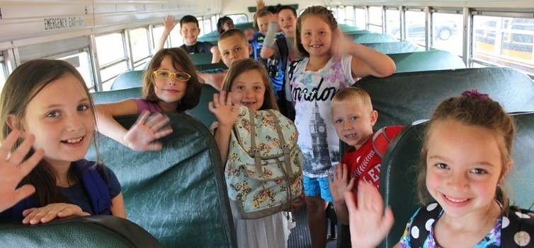 students smiling and waving inside bus