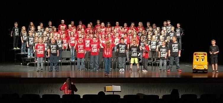 several kids on risers on stage most wearing red t-shirts