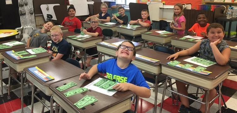 Mrs. Rinehart's  math class is using $100, $10, and $1 bills to learn about place value.