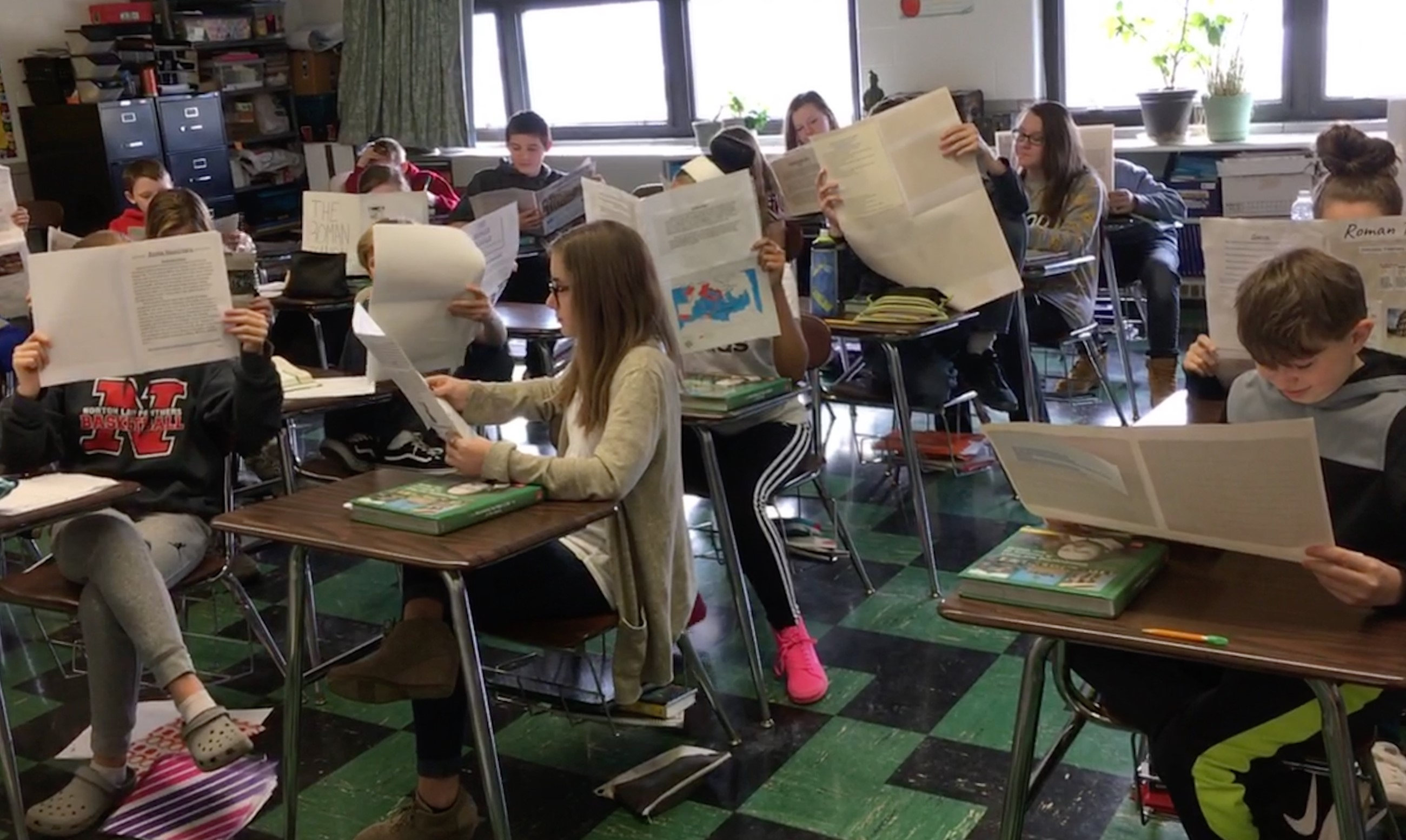 Students in Mrs. Majewski's World History class reading the newspapers they created for a class project.