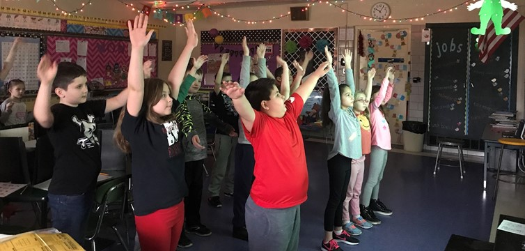 Second graders in Mrs. Myers' class take a brain break to stretch and refocus.