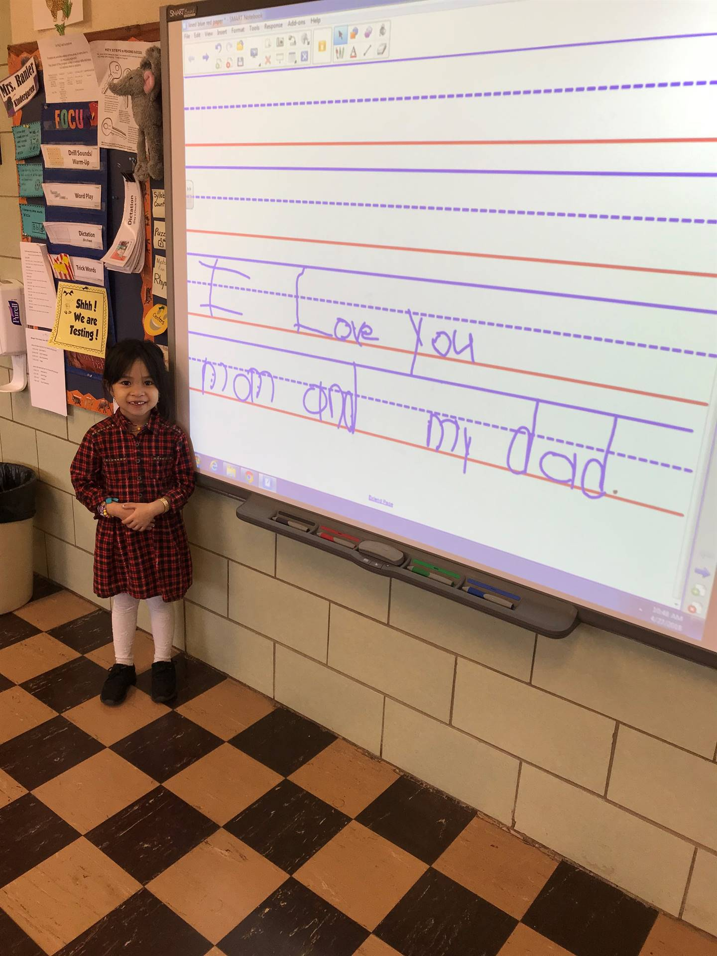 Kindergarten students use the SMARTboard in Title 1 to show what they know about writing.