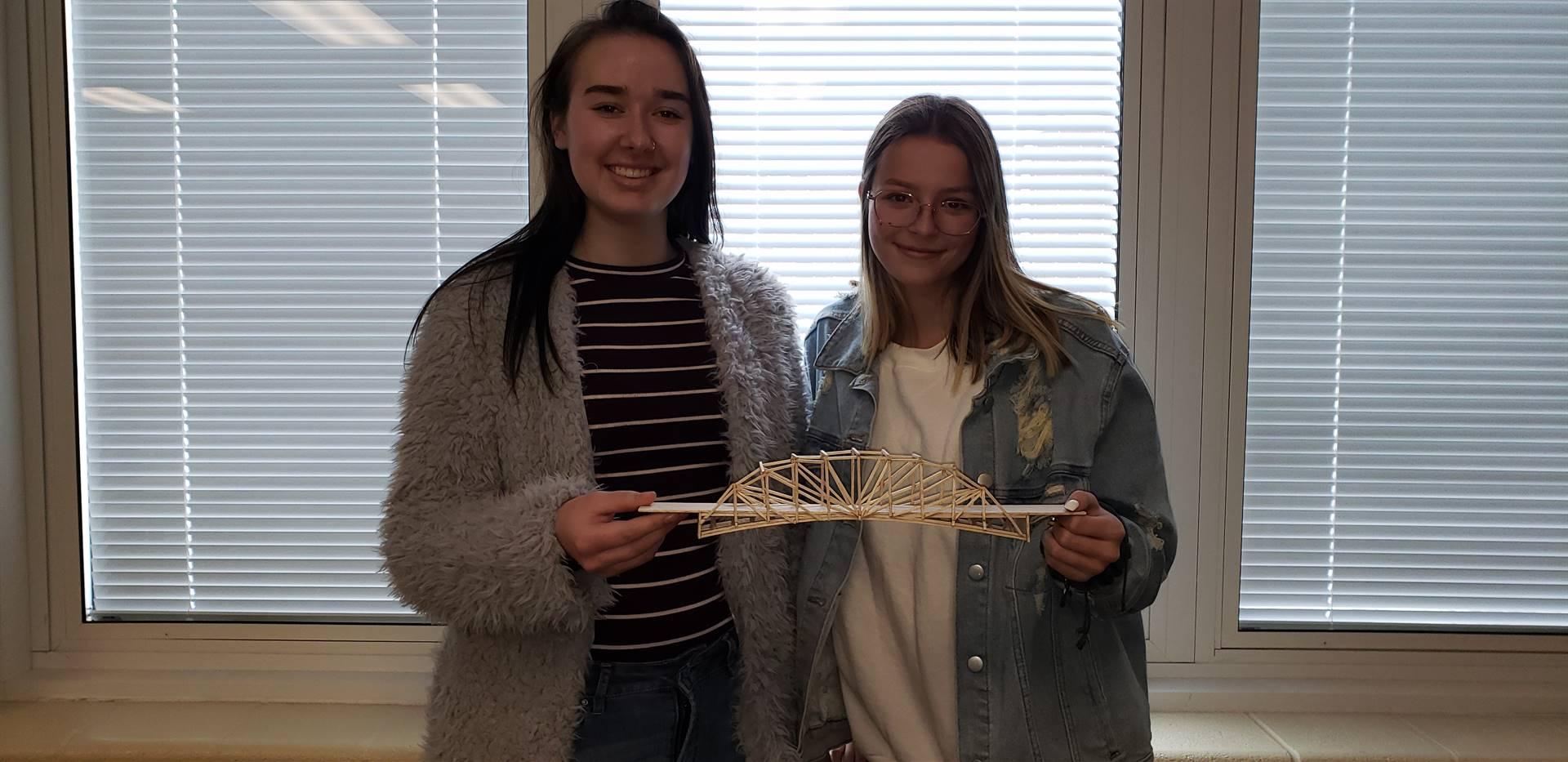 Physics Students Displaying Their Miniature Balsa Bridges