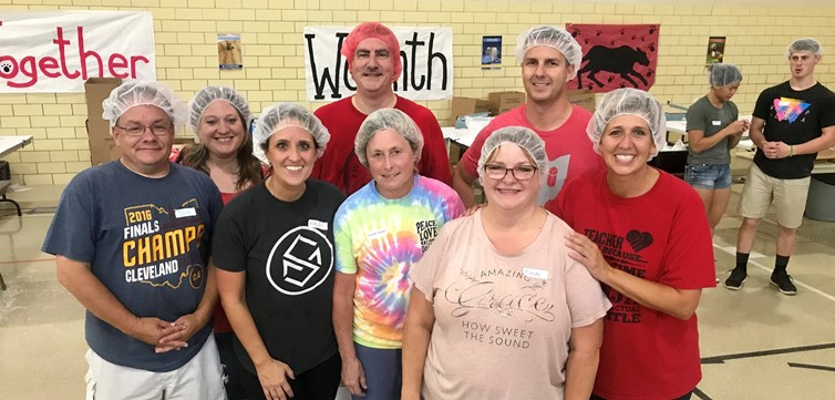 N.E.S. staff rocking the hair nets at the Feed My Starving Children packing event. We Roar. Together.