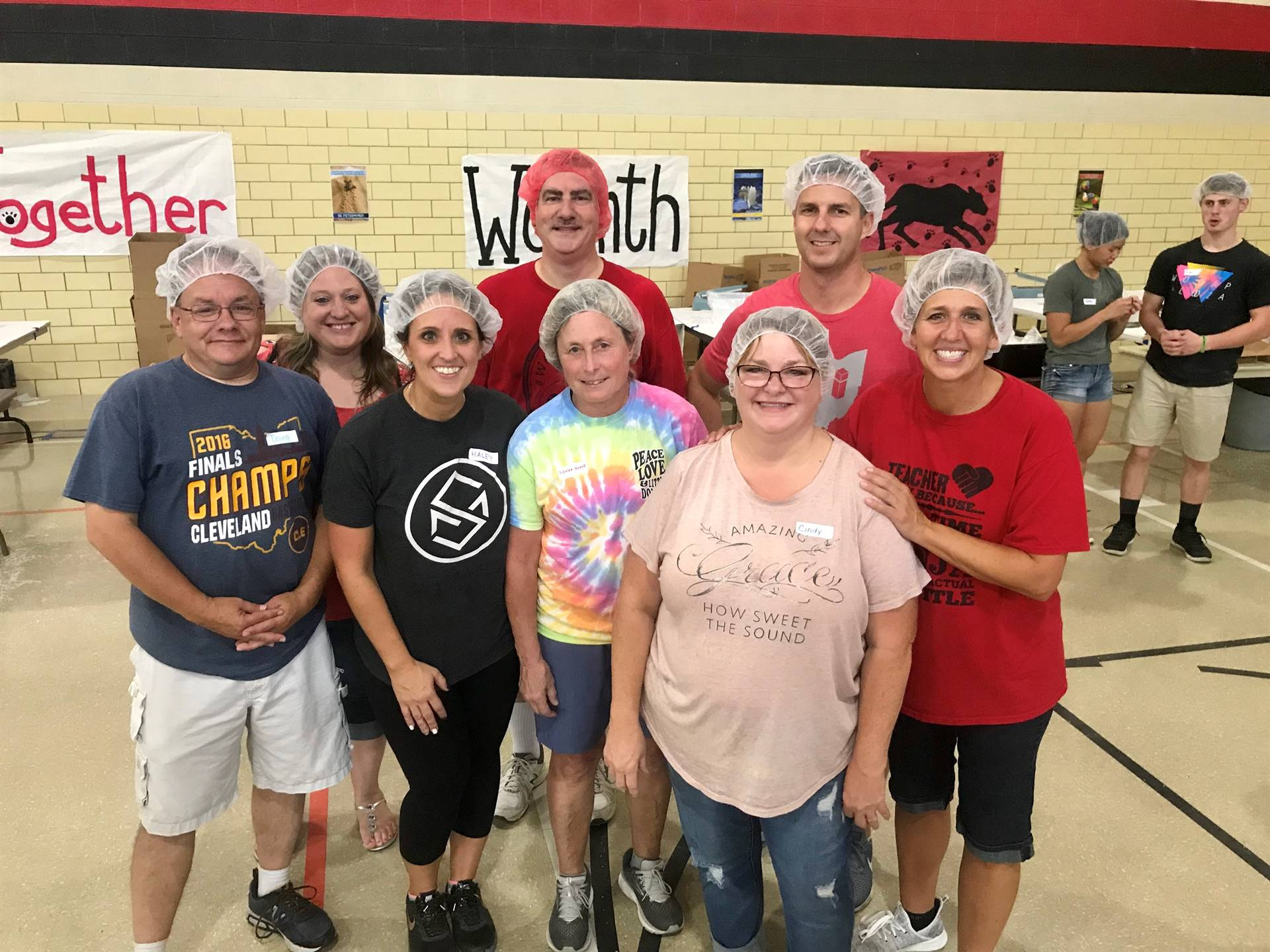 N.E.S. staff rocking the hair nets at the Feed My Starving Children packing event. We Roar. Together